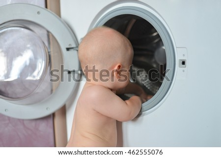 Little baby boy loading clothes into washing machine