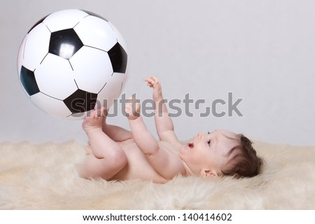 Little baby boy, lying naked on her back on woolen fleece; holding big soccer ball, on white background - stock photo