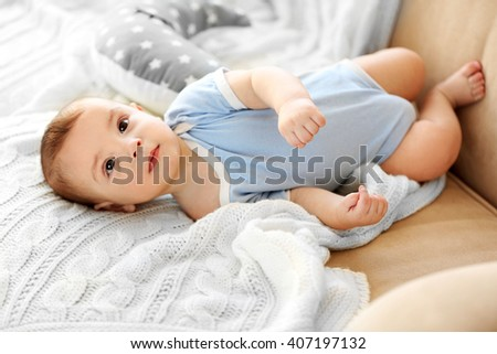 Little baby boy lying on a couch at home - stock photo