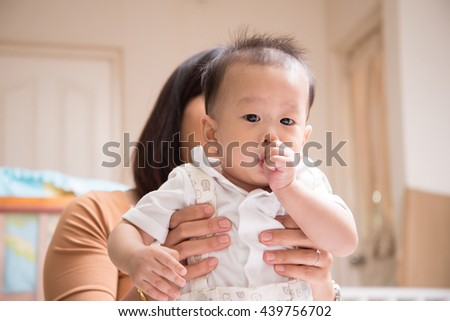 Little baby boy 7 months sucking his thumb finger in the mouth - stock photo