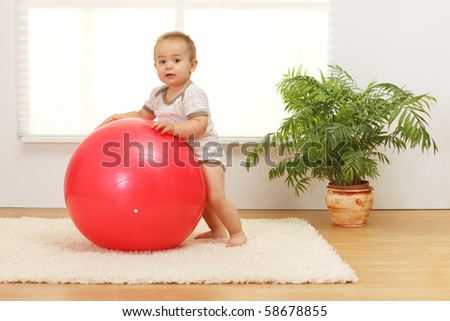 Little baby boy playing with big red ball - stock photo