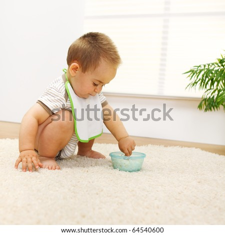 Little baby boy playing with food alone - stock photo