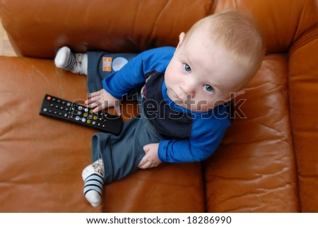 Little baby boy playing with TV remote - stock photo