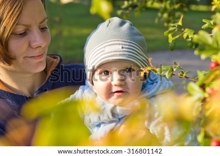 Little baby boy sitting on mother hands and smiling - stock photo