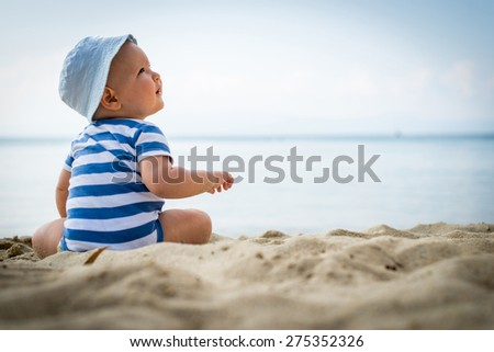 Little baby boy sitting on the sand - stock photo