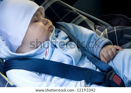 little baby boy sleeping in safety car seat - stock photo