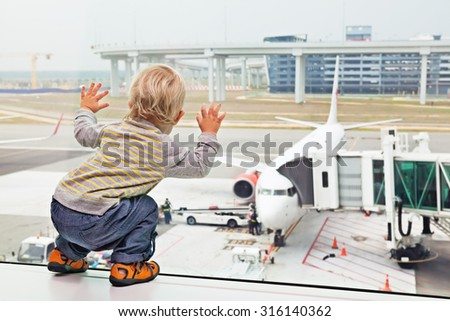 Little baby boy waiting boarding to flight in airport transit hall and looking through the window at airplane near departure gate. Active family lifestyle, travel by air with child on summer vacation - stock photo