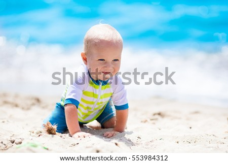 Little baby boy wearing blue rash guard suit playing on tropical ocean beach. UV and sun protection for young children. Toddler kid during family sea vacation. Summer water fun