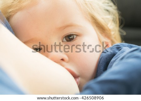 Little baby boy with blonde hair sucking female breast outdoor closeup - stock photo