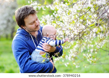Little baby boy with his middle age father in the blossom garden  - stock photo