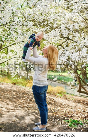 Little baby boy with young mother in the spring blossom garden - stock photo