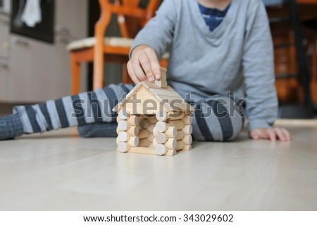 Little baby building wooden blocks to build little house