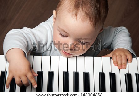 little baby child  play music on black and white piano keyboard - stock photo