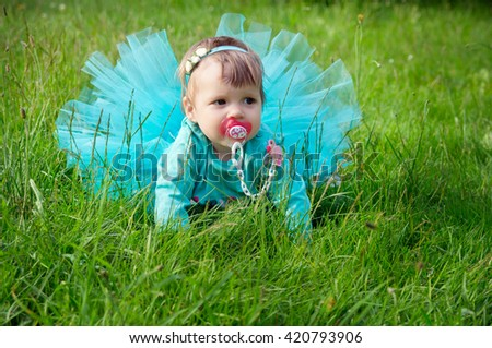 Little baby crawling on grass outdoors