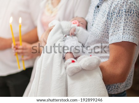 Little baby cute feets on parents hand in church - stock photo