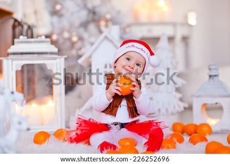 Little baby dressed as Santa helper playing on the floor. Christmas decorations. Beautiful interior. - stock photo
