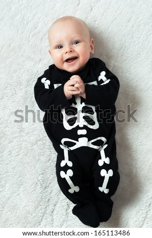 Little baby dressed funny skeleton - stock photo