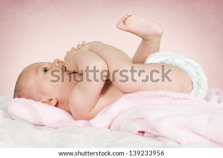 Little baby eating her feet - stock photo