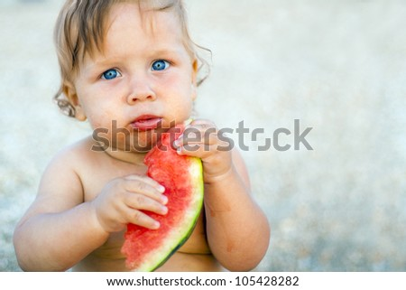 little baby eating watermelon outdoors - stock photo