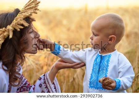 Little baby feeding mother in a barley field