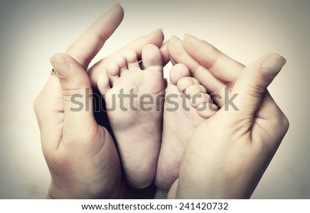 Little baby feet in mother's hands - stock photo