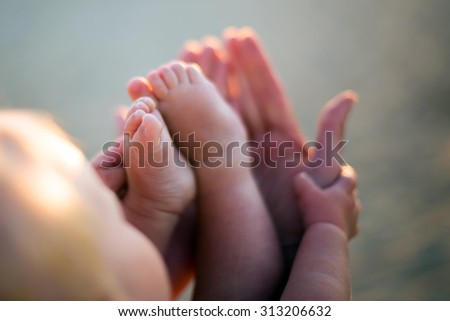 Little baby feet on mothers hands outdoors at backligh. Shallow depth of field. Baby finger in a focus. - stock photo