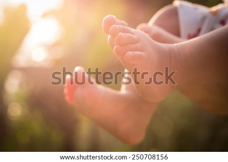 Little baby feet on nature outdoors. summer park in background - stock photo