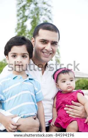 little baby girl and a little boy sitting in the lap of the father - stock photo
