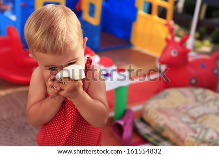 Little baby girl blowing her nose - stock photo