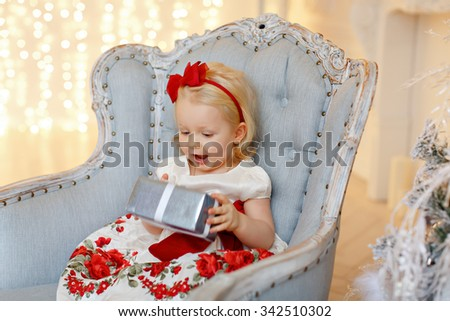 Little baby girl charming blonde in a red dress sitting in a chair against a background of Christmas trees and wonders present, in the interior of the house - stock photo