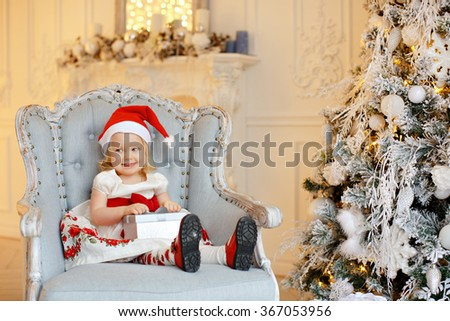 Little baby girl charming blonde in a red santa hat, smiling and sitting in a chair against a background of Christmas trees and holding a gift, in the interior of the house - stock photo