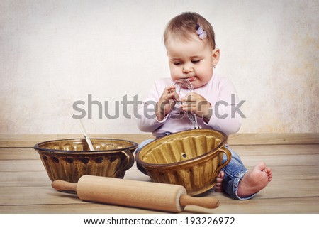 Little baby girl cooking - stock photo