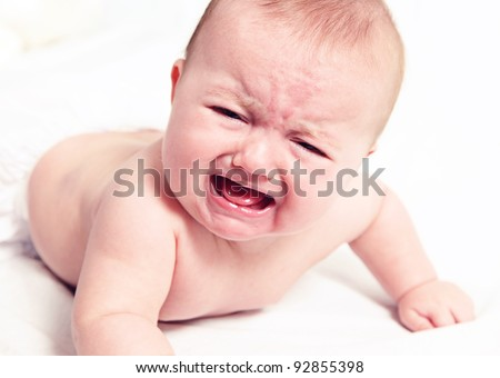 Little baby girl crying on white blanket - stock photo