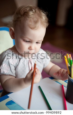 Little baby girl drawing with colorful pencils