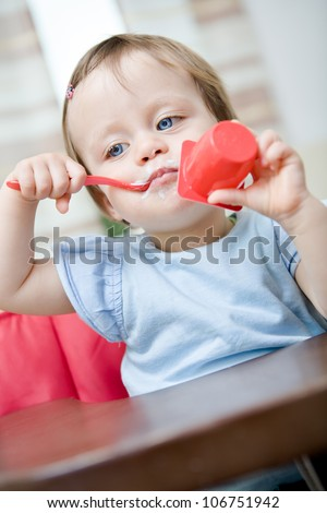 little baby girl eating a yogurt