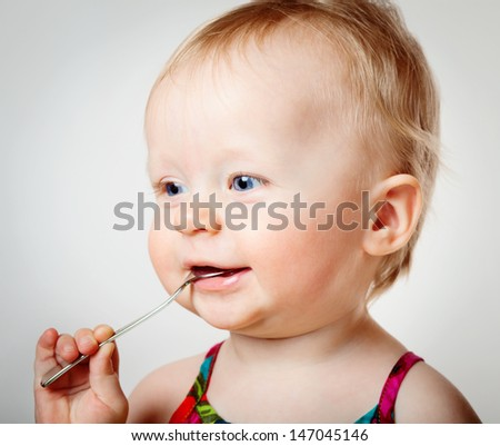Little baby girl eating with spoon