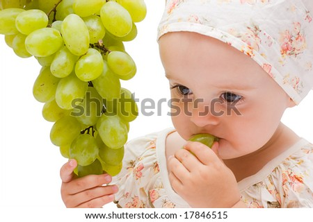 Little baby girl eats the big grapes, isolated on white - stock photo