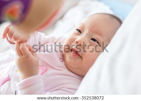 Little baby girl have funny time while lying