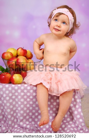 little baby girl hiding  apples and sitting next to large glass bowl of fresh fruits - stock photo