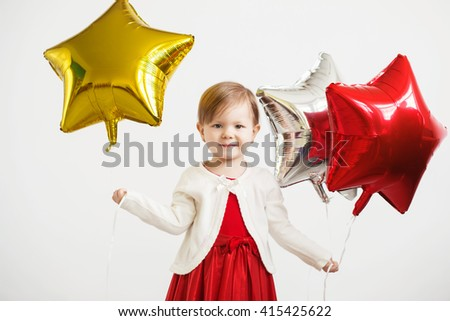 Little baby girl holding balloons in the form of stars. Young girl holding a star-shaped balloons. Happy child with colorful shiny foil balloons against a white background - stock photo