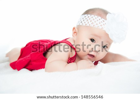 Little baby girl in red dress lying on a blanket, isolated on white background - stock photo