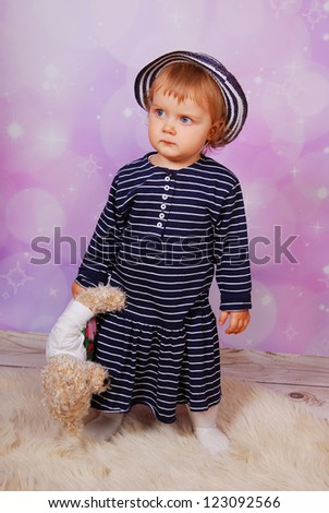 little baby girl in striped dress and hat holding teddy bear - stock photo