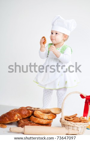 Little baby girl in the cook costume standing near bread rolls and bagels. She is eating bagel.