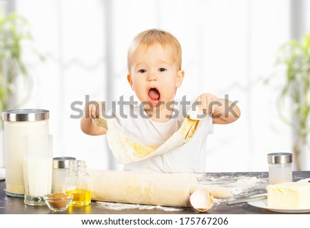 Little baby girl is cooking, baking, pastry rolls out - stock photo