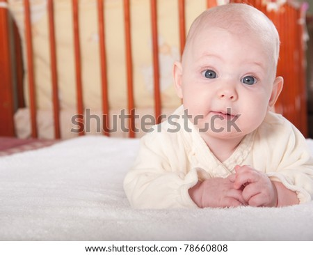 Little baby girl is lying near her bed - stock photo
