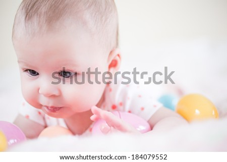 Little baby girl playing with Easter eggs.