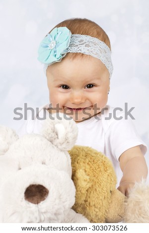 Little baby girl playing with plush toys - stock photo
