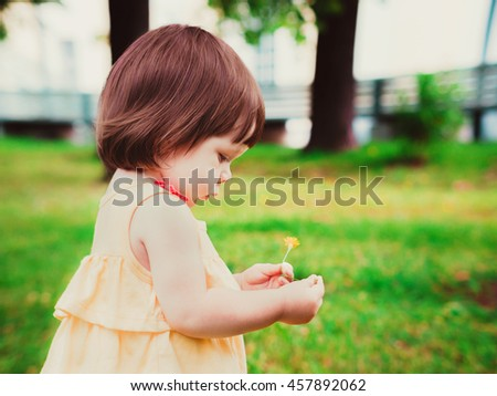 Little Baby Girl Portrait in profile outdoor. Cute Child over nature background. Adorable one year old baby with flower in hands - stock photo