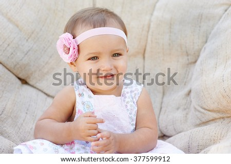 Little baby girl poses on a white chair.  She is smiling happily.