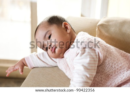 little baby girl resting on the arm of sofa seat - stock photo